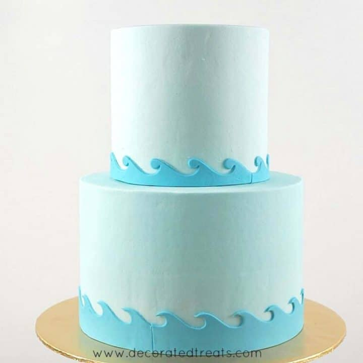 2 tier round cake in light blue fondant and wavy fondant borders