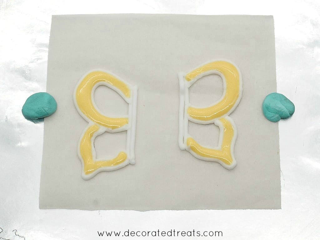 2 wings of a royal icing butterfly in orange and yellow on a parchment square
