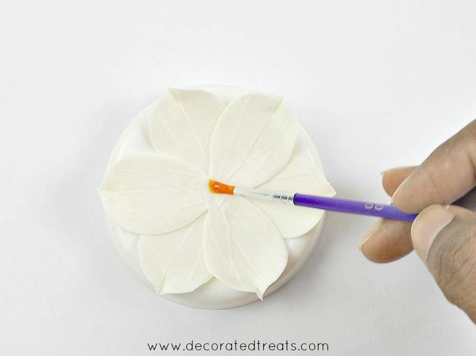 Using a purple brush to apply glue to the center of a gum paste flower