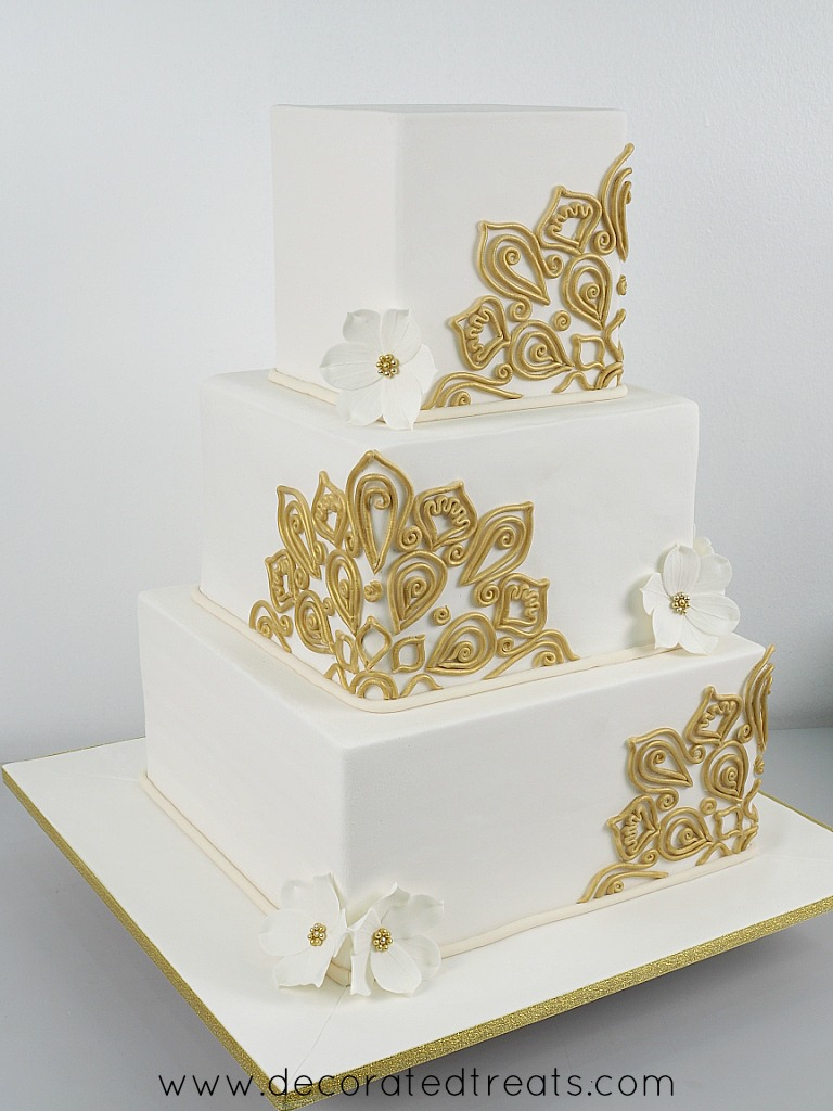 A 3 tier square cake in white, with gold lace and white gum paste flowers