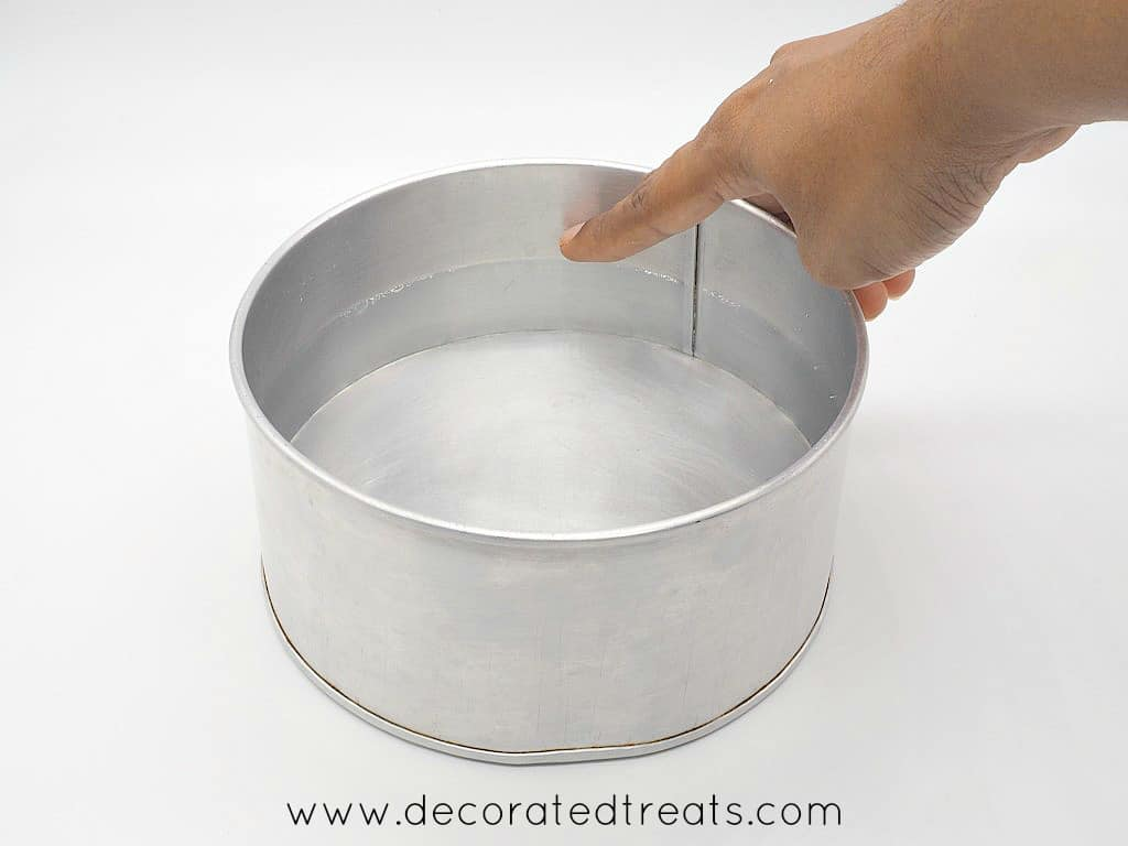 Pointing to the water level in a cake tin filled with water