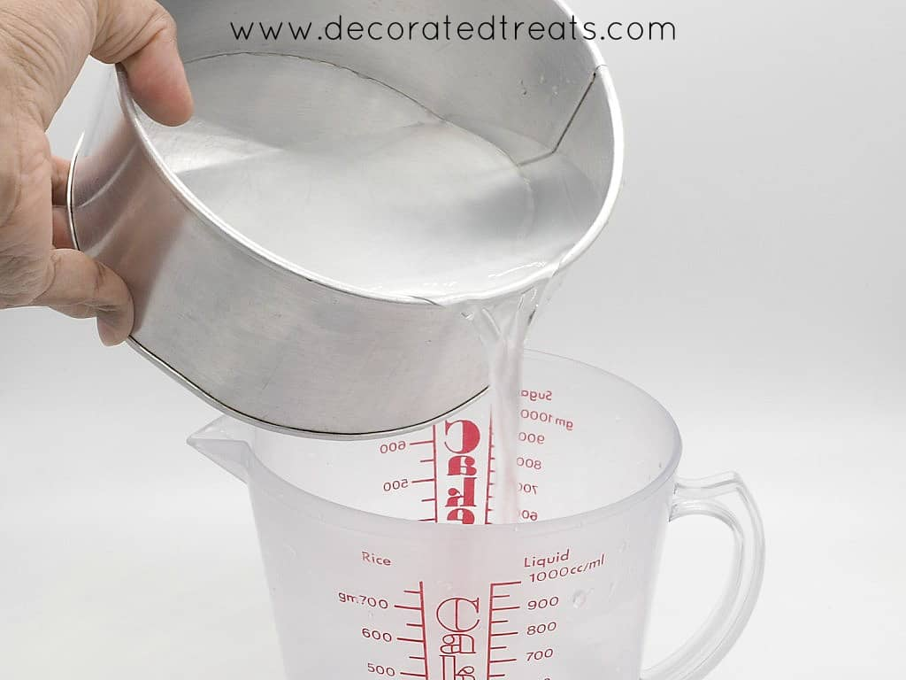 Pouring water from a cake tin into a measuring jug