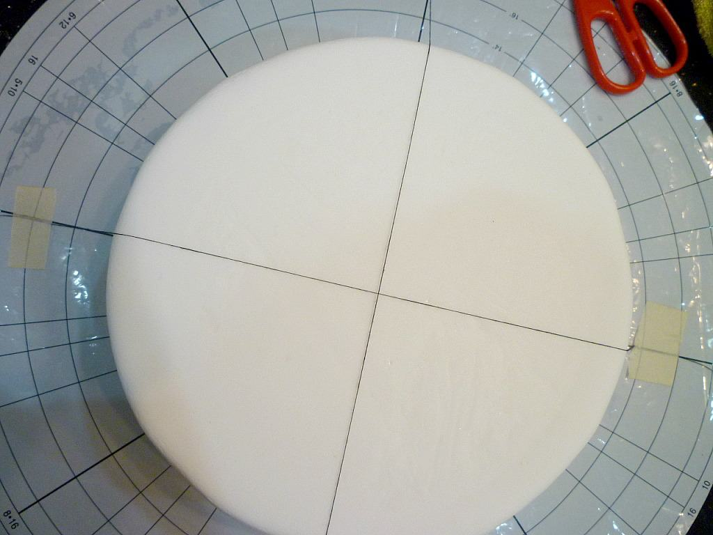 Black thread in a cross pattern on a white fondant covered cake
