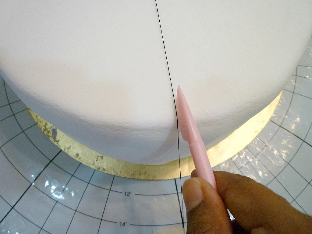 Marking a white fondant covered cake with a pink tool
