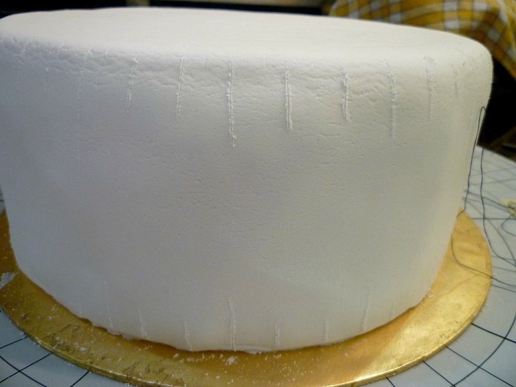 Lines marked on the edges of a white fondant covered cake