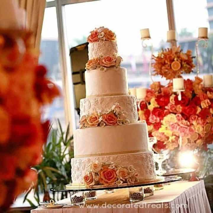 A 5 tier wedding cake decorated in orange and yellow