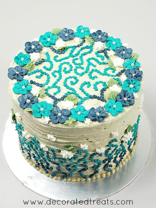 A round cake decorated in blue and turquoise piped buttercream flowers and dot piping