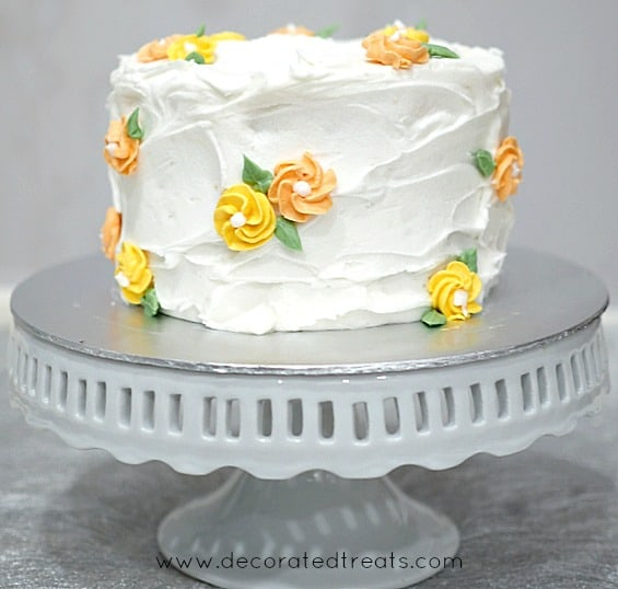 A round cake in white buttercream and yellow and orange piped buttercream roses