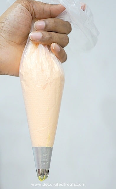 Holding a piping bag filled with orange icing and fitted with a large piping tip.