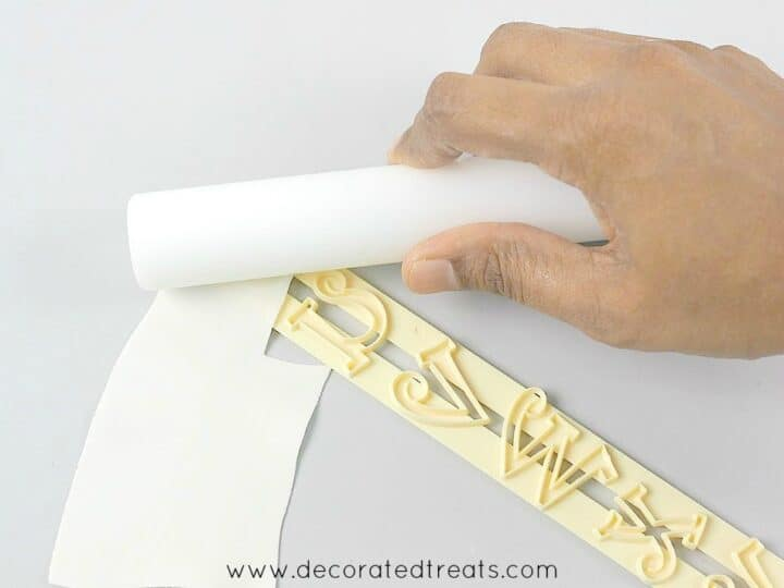 Using a rolling pin to rub on a piece of gum paste on a letter cutter
