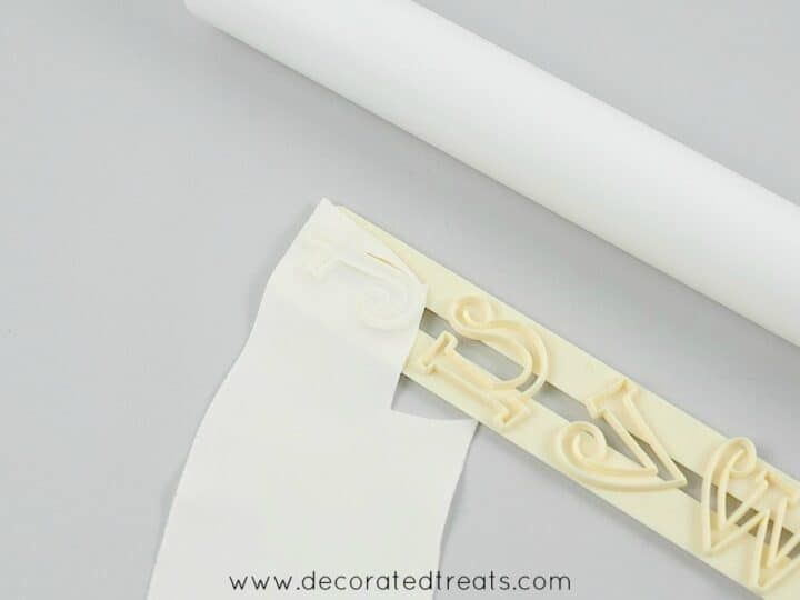 A piece of gum paste on a letter cutter