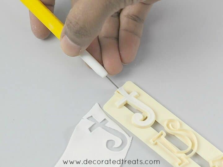 Using a needle tool to remove the gum paste from the alphabet cutter