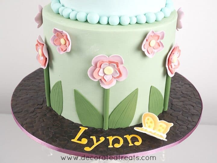 A round floral cake with the name Lynn on the cake board.