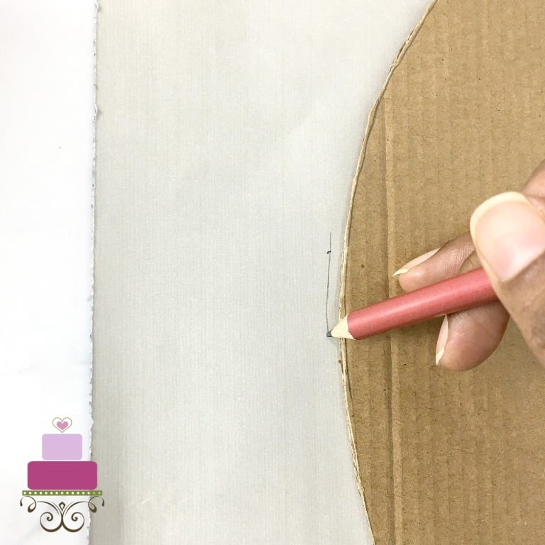 Marking the outline of a brown cardboard cutout onto a white paper with pencil