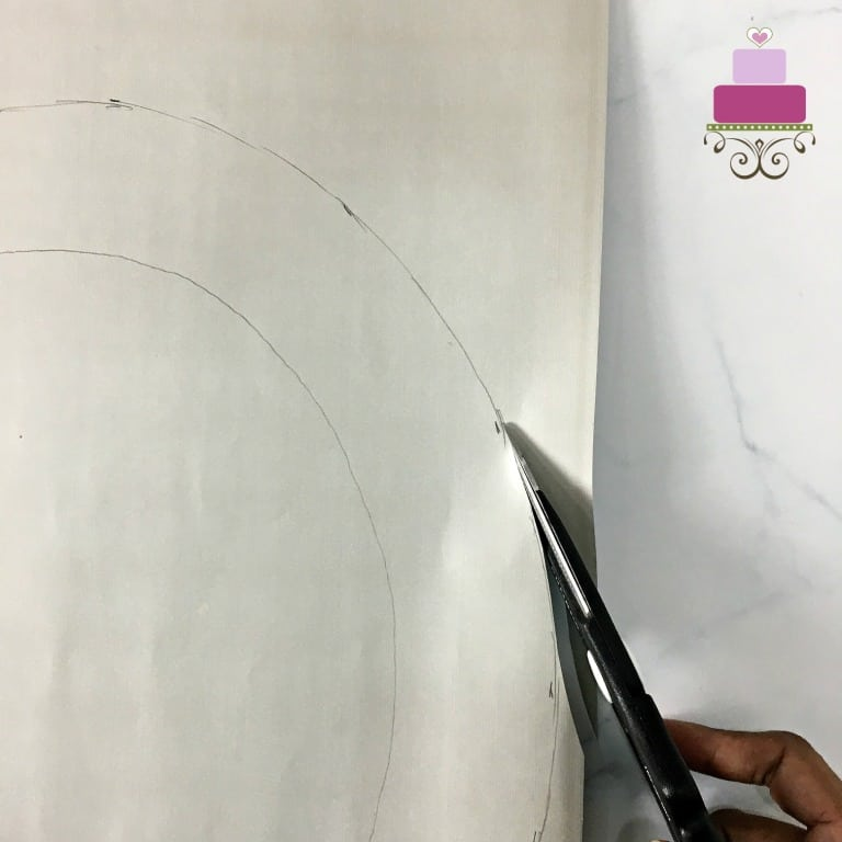 Using scissors to cut the outline of a paper template