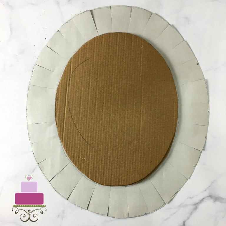 A brown cardboard cutout on a slightly larger piece of oval paper, with the sides slit in equal intervals