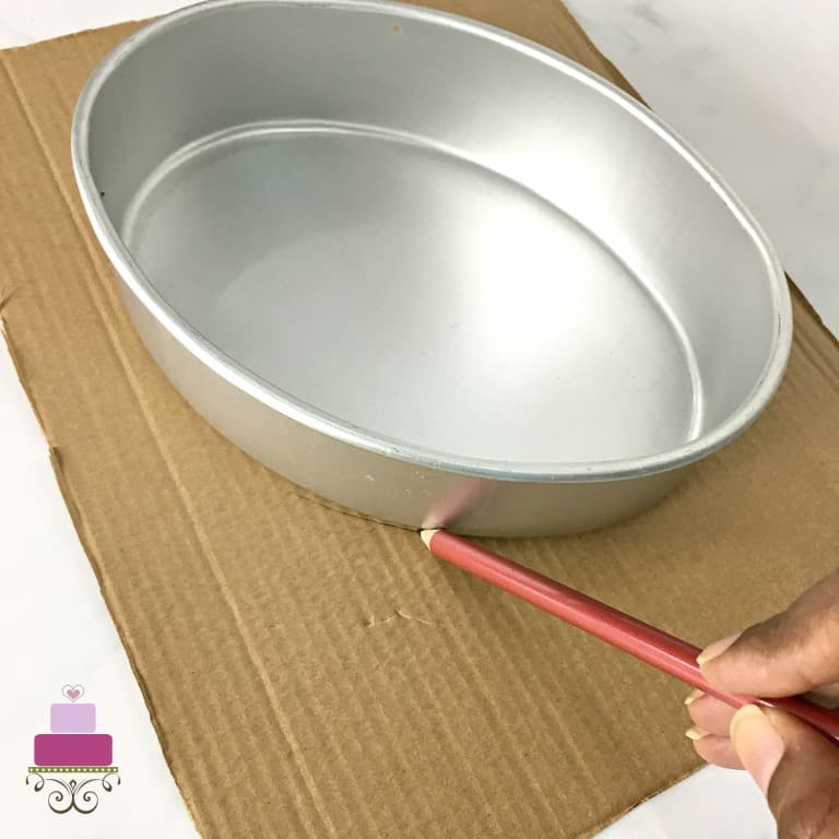 An oval cake tin on a cardboard, with a hand tracing the outline