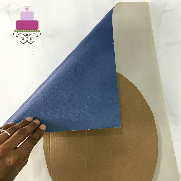 An oval shaped brown cardboard on the reverse side of a blue wrapping paper