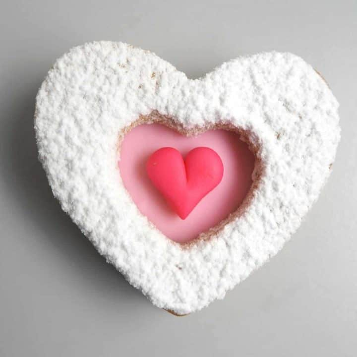 A heart shaped cookie decorated in pink heart and icing sugar