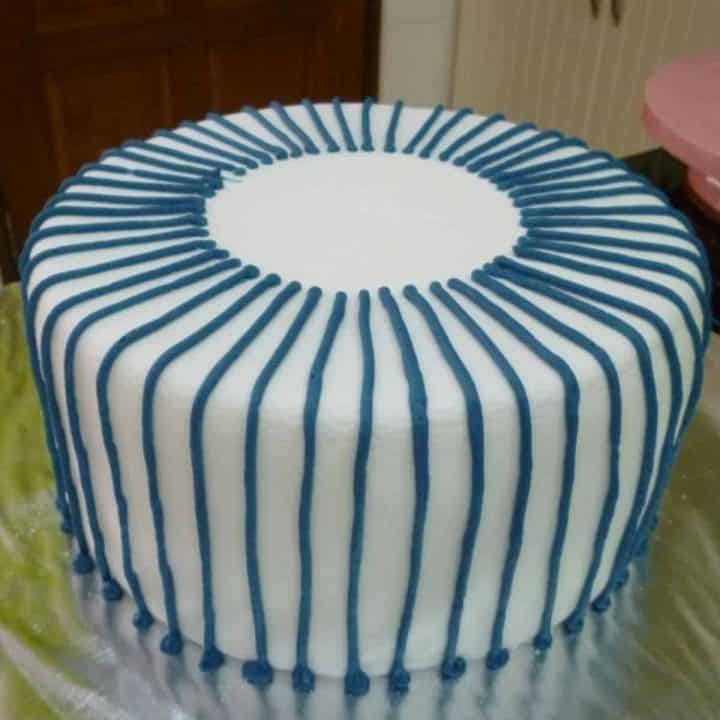 Blue lines piped all around a round cake