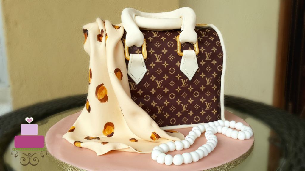An LV inspired handbag cake with a leopard print fondant scarf