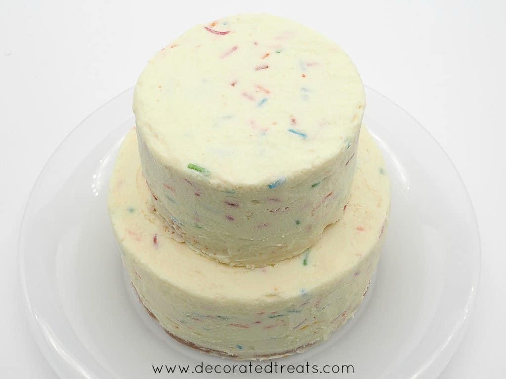 A 2 tier cake covered in confetti buttercream