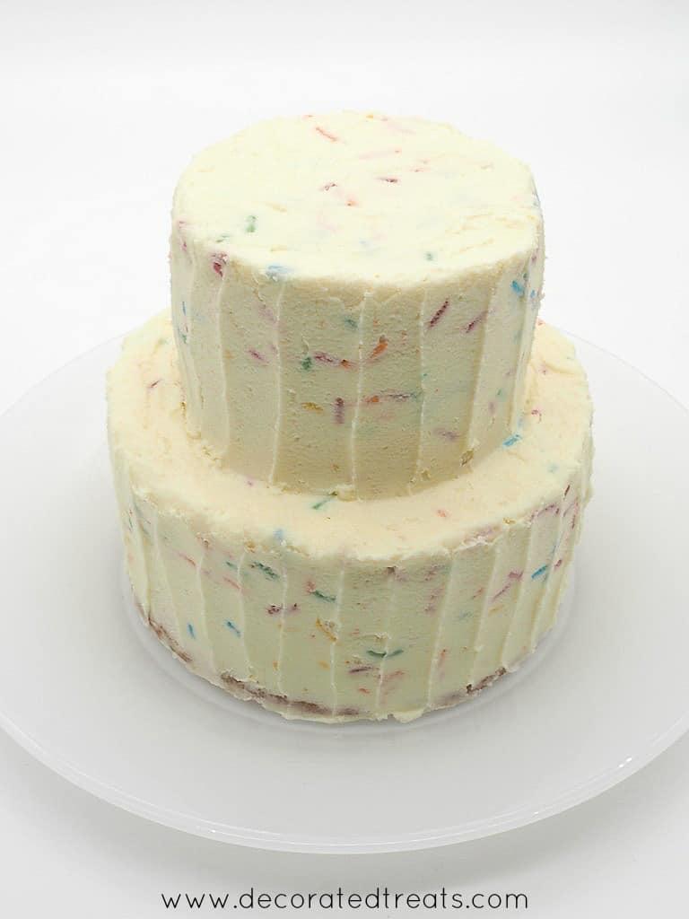 A two tier cake covered in confetti buttercream