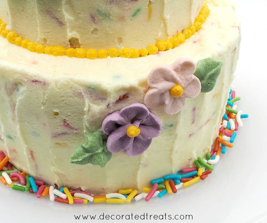 2 purple flowers on a confetti buttercream covered cake. Cake border is decorated with colorful confetti.