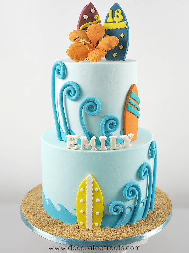 A two tier beach themed cake with fondant waves, surf boards and gum paste hibiscus