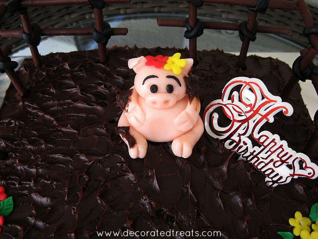 A pink pig fondant topper on a a chocolate covered cake