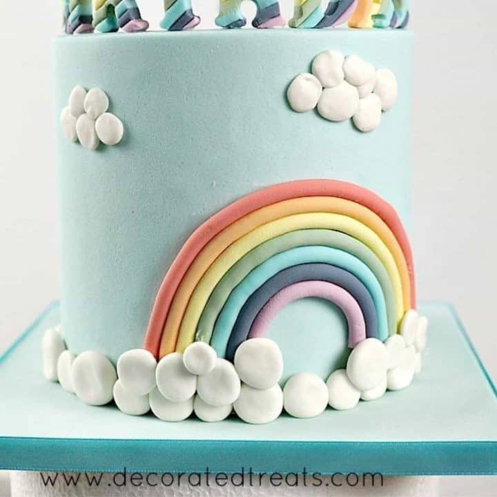 A rainbow cake decorated with fondant clouds