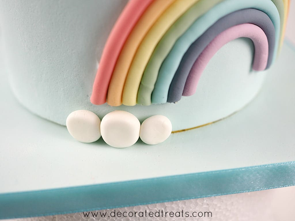 3 patches of white fondant at the border of cake decorated with fondant rainbow