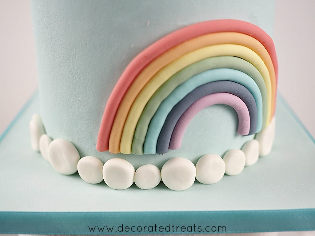 A row of white fondant patches at the base of a cake and a fondant rainbow on top
