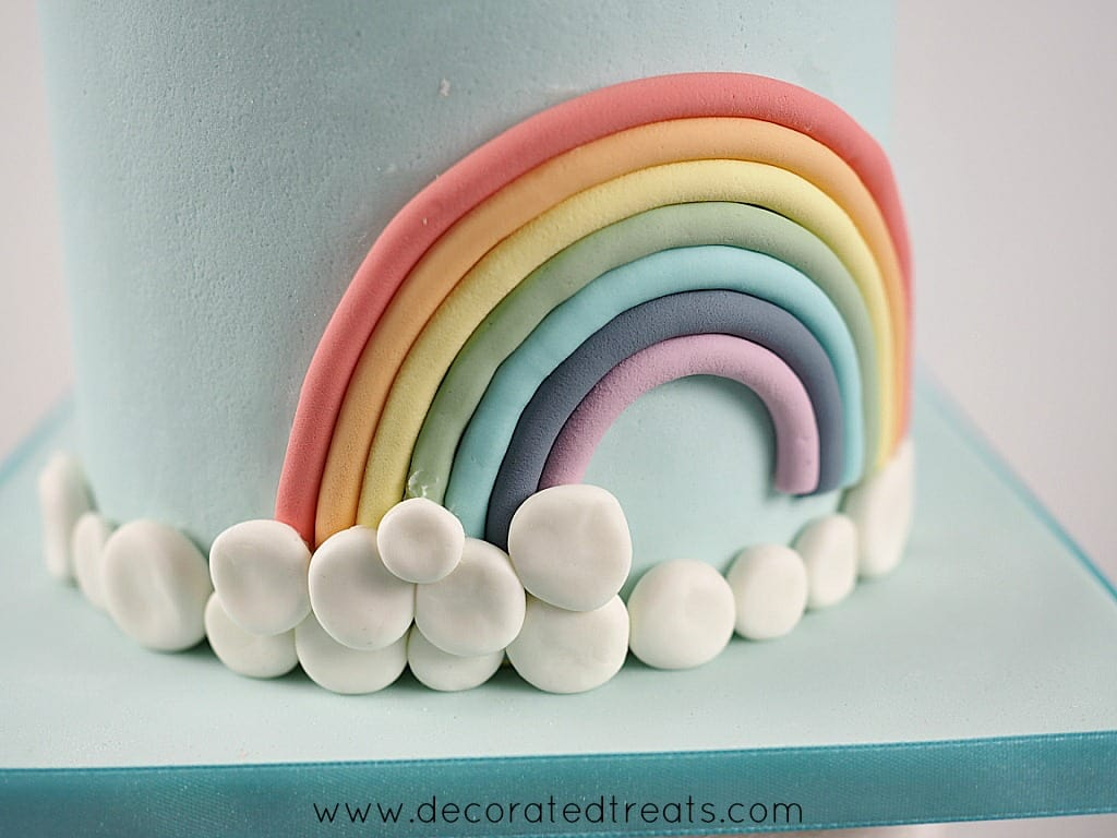 A cake decorated with fondant rainbow and a border of white fondant patches as the clouds