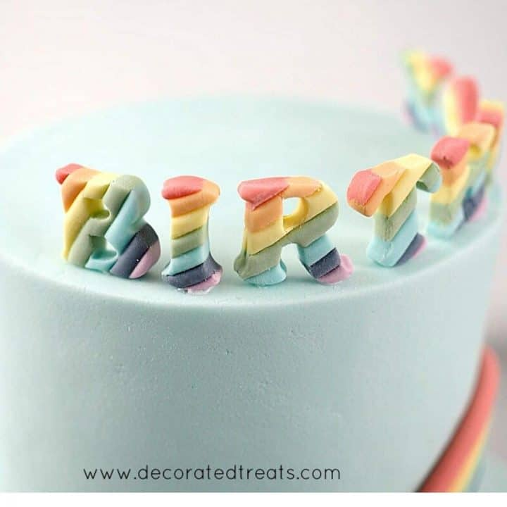 Rainbow colored fondant letters on a cake