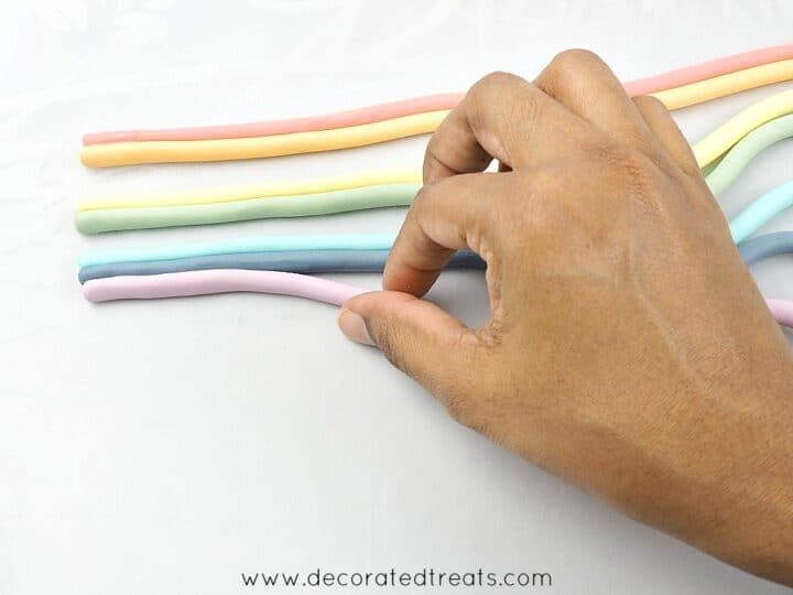 Pushing rainbow colored fondant strips together with hand