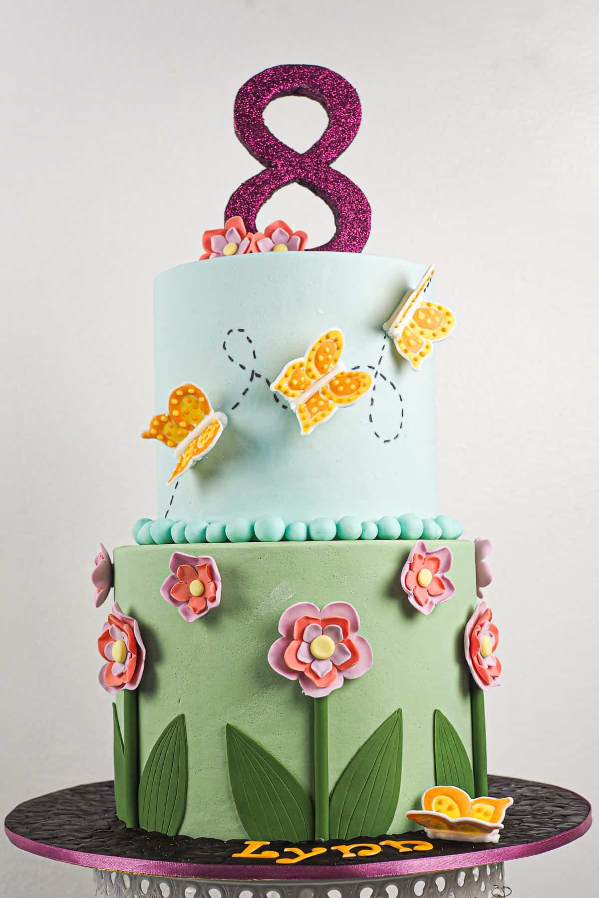 A 2 tier flowers and butterflies themed cake with royal icing butterflies and a number 8 topper