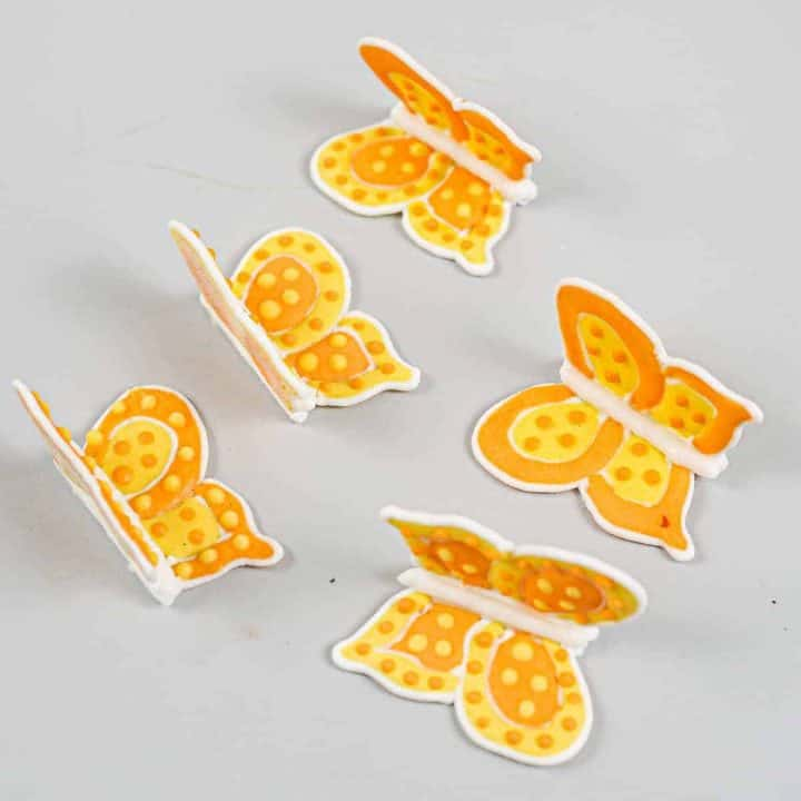 Orange and yellow royal icing butterflies against a grey background