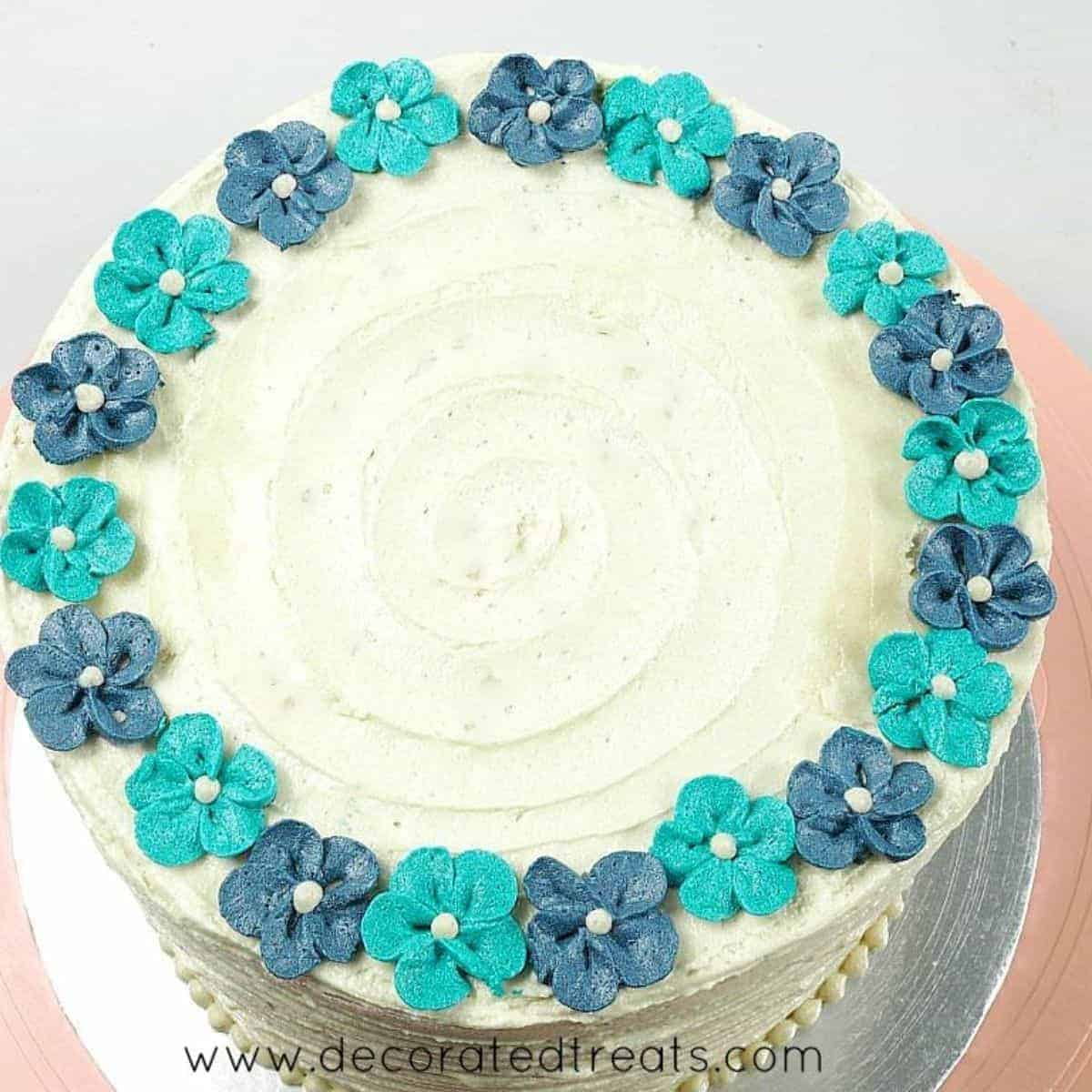 Turquoise and blue buttercream flowers arranged in a circular pattern around the top edges of a round cake covered in buttercream