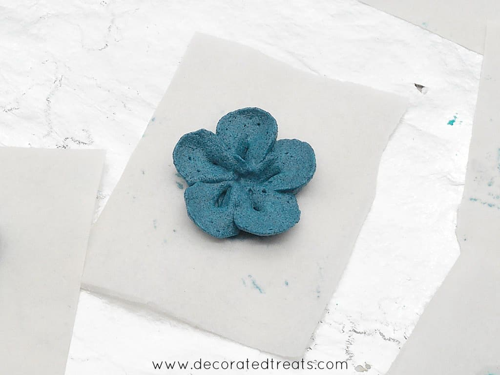 Dark blue buttercream flower on a parchment square
