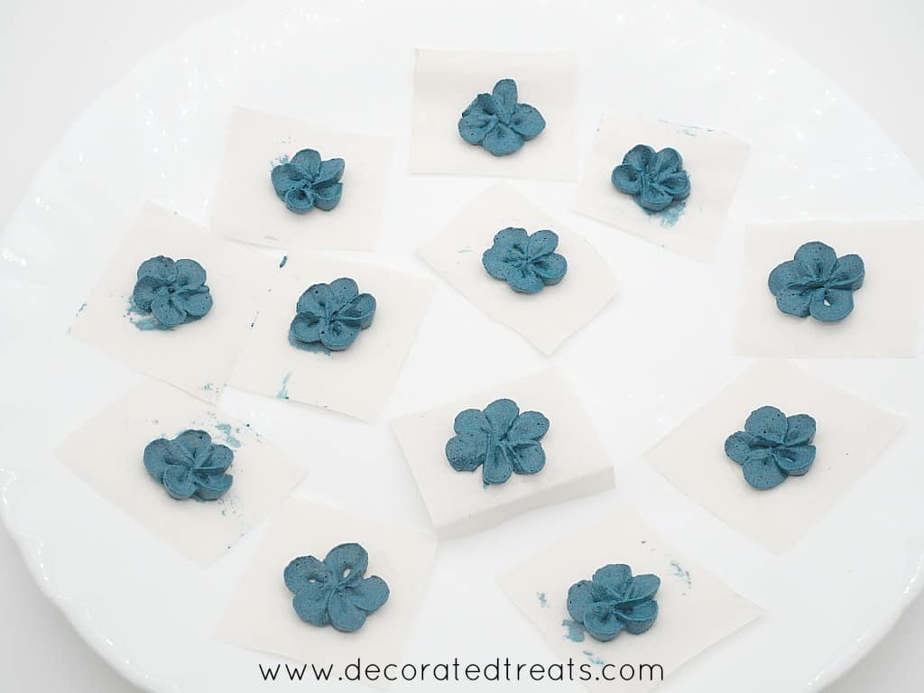 Dark blue buttercream flowers on parchment squares