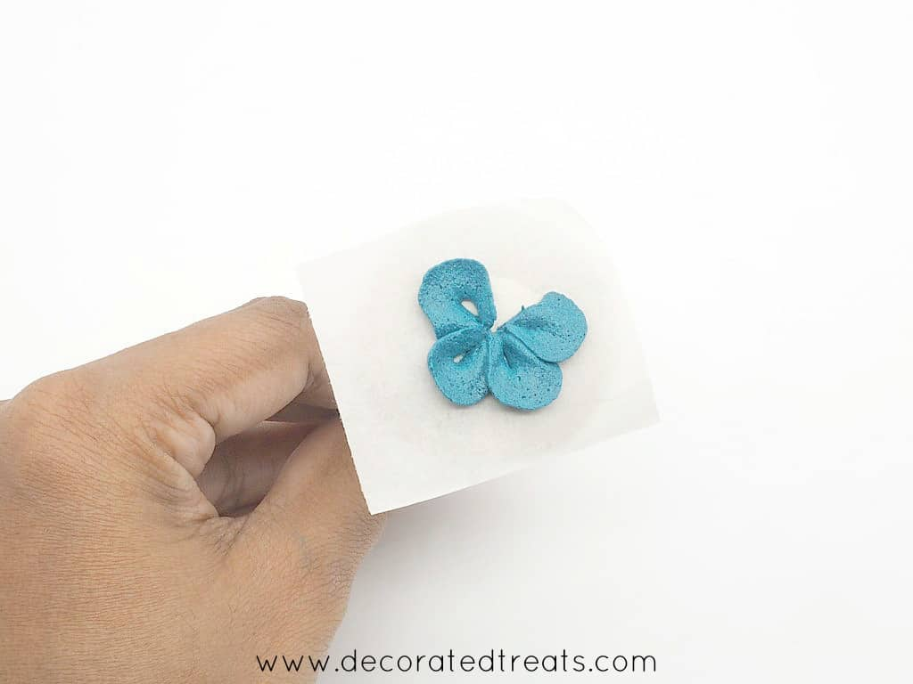 4 petals of a buttercream flower in blue piped on a parchment square held on a flower nail