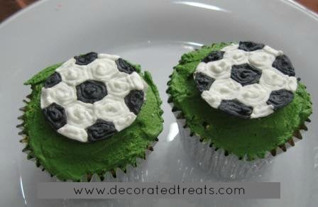 2 cupcakes with soccer ball toppers