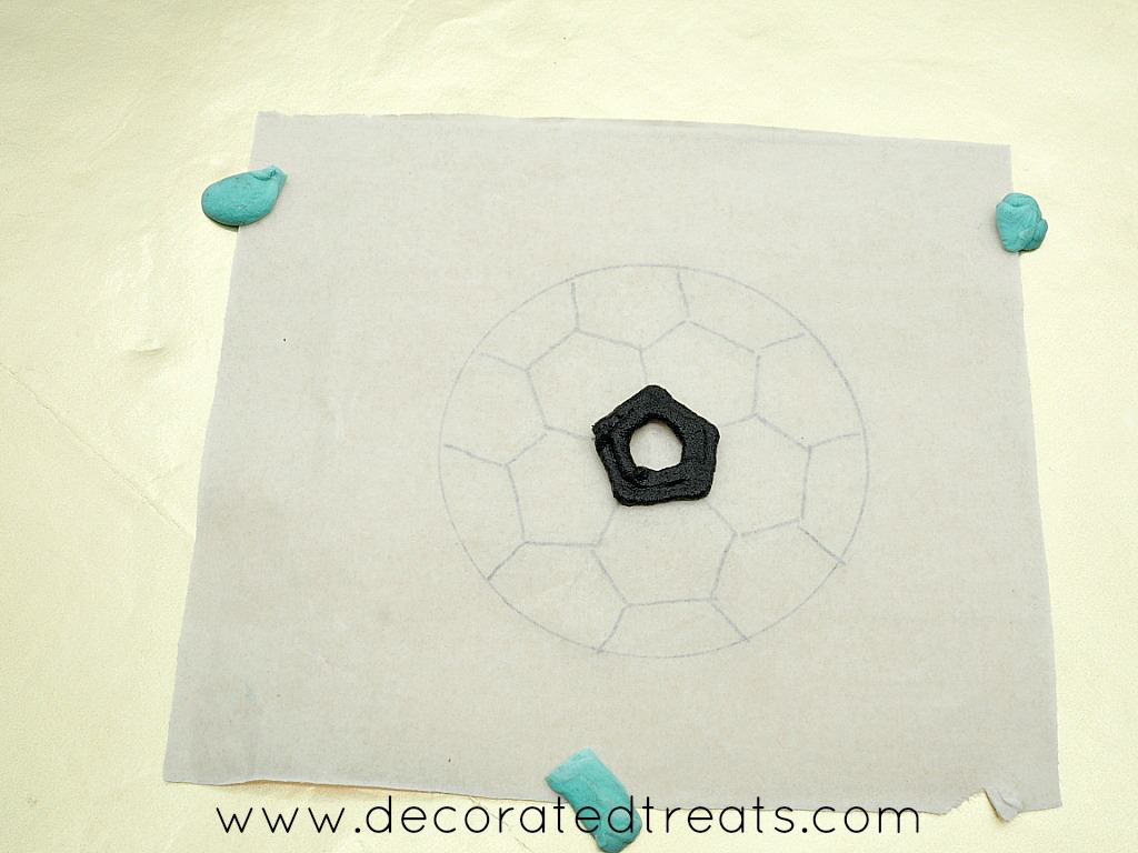 Black outline piping on a soccer ball parchment template