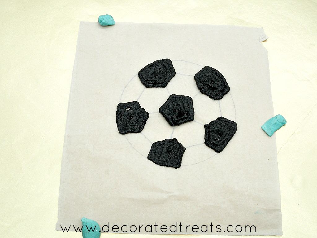 Black sections of a soccer ball parchment template filled with black icing
