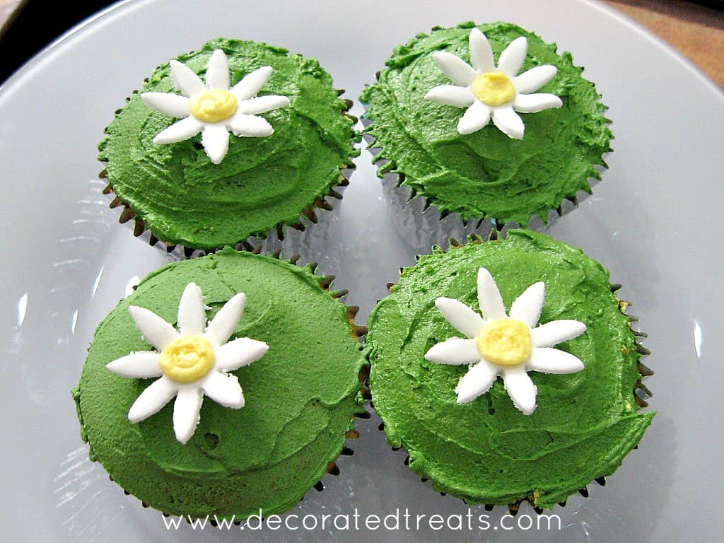 4 cupcakes in a plate decorated with green icing and fondant daisies