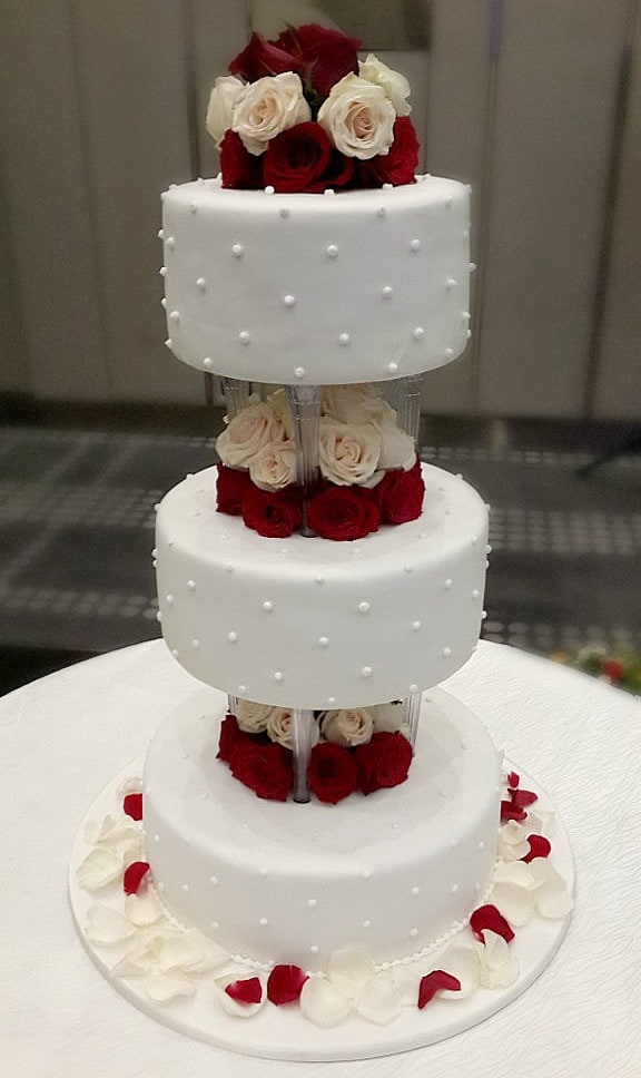 A 3 tier round cake on pillars with fresh red roses