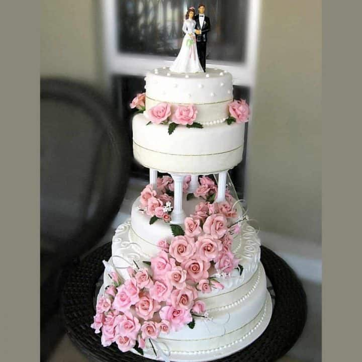 A 4 tier cake stacked on pillars, decorated with pink roses and a bride and groom topper
