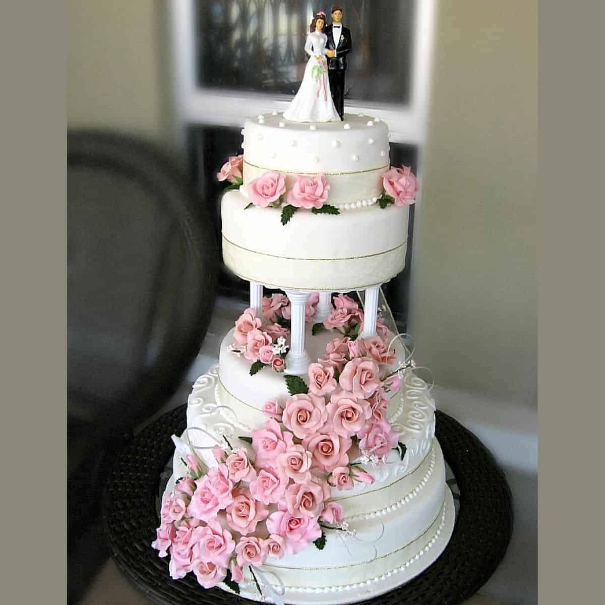 A 4 layer cake stacked on pillars, decorated with pink roses and a bride and groom topper
