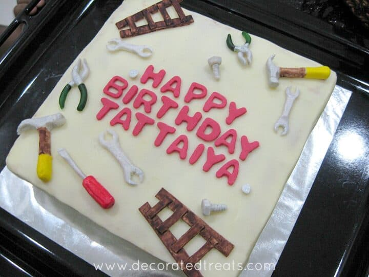 A square birthday cake with fondant hammer, screwdriver, bolts, nuts and ladder.